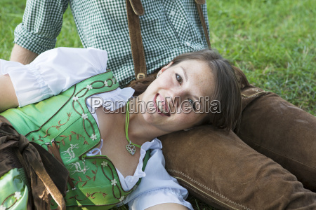 bavarian couple sitting on the grass