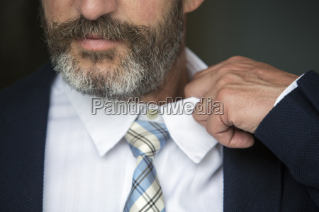closeup of man loosens his shirt