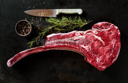 raw tomahawk beef steak with ingredients