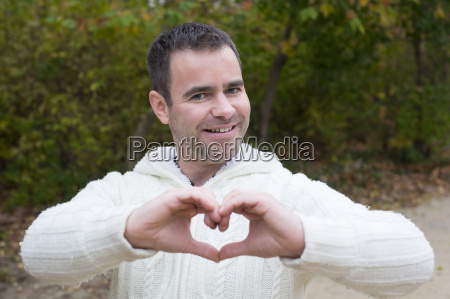 man outside shaping heart with his