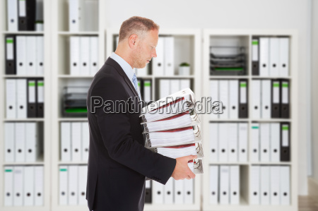 mid adult businessman carrying binders in