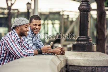 two men side by side leaning