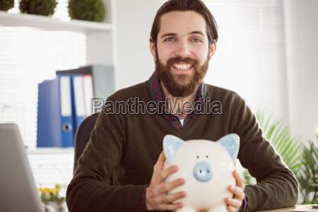 hipster businessman with a piggy bank