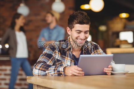 smiling hipster sitting and using tablet