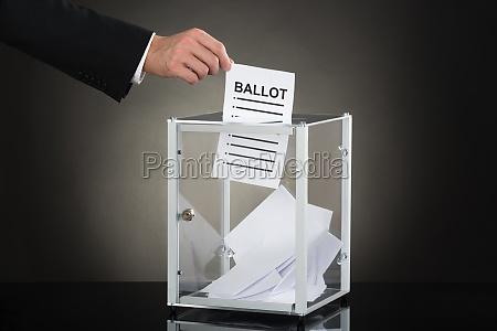 businessperson hand putting ballot in glass