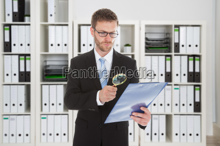 businessman looking at document through magnifying