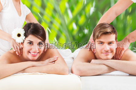 happy young couple receiving shoulder massage