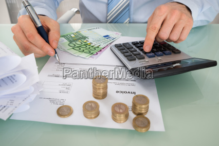 businessman calculating invoice with money at