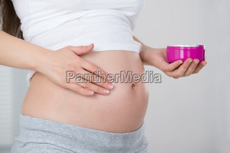 pregnant woman applying cream on her