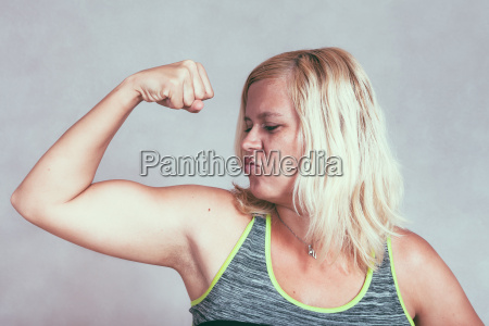 strong muscular sporty woman flexing biceps