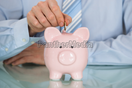 businessman inserting coin in piggy bank