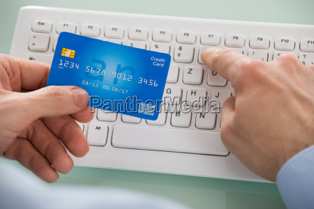 persons hand holding card while using