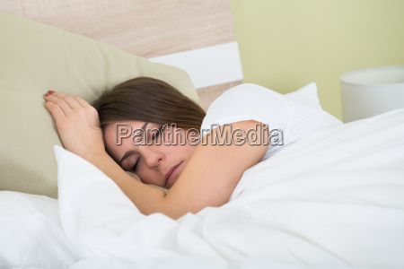woman sleeping on bed with an