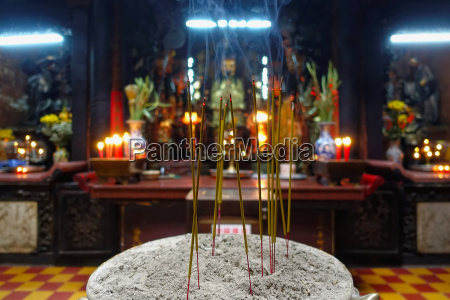 burning incense candles infront of a