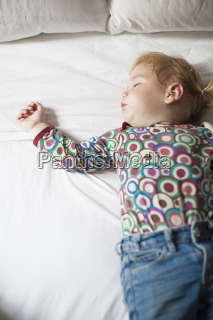 colored shirt baby sleeping on white