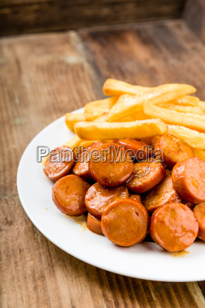 currywurst with fries on a wooden