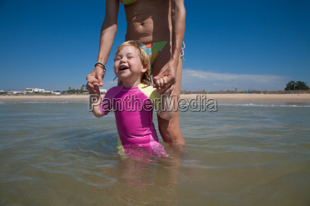 happy baby with mom at ocean