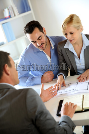couple meeting real estate agent to