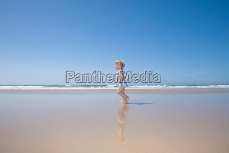 baby running at seashore