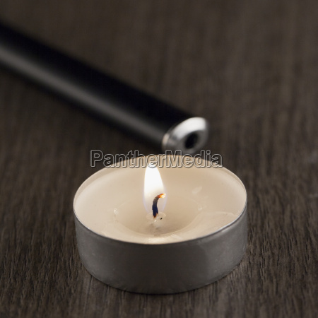 lit candle over table