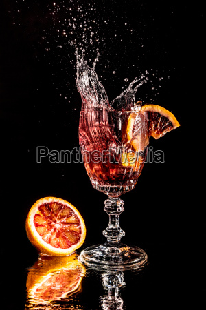 orange slice falls into a champagne