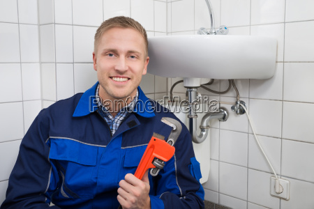 plumber holding wrench sitting next to
