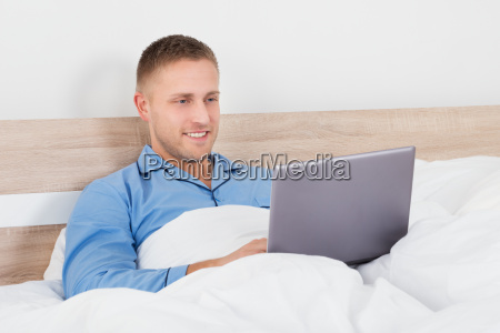 man using laptop on bed
