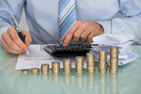 businessman calculating bills in front of
