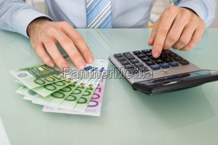 businessperson with banknote and calculator