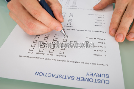 person hand filling customer satisfaction form