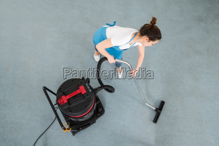 female janitor cleaning floor with vacuum