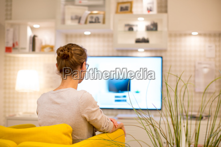 pretty young woman watching tv at