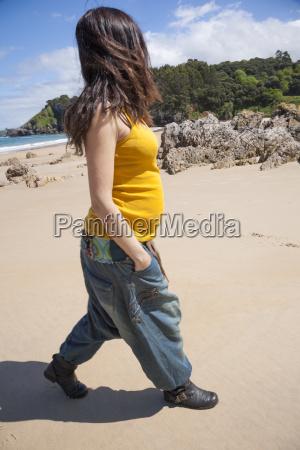walking pregnant woman at beach