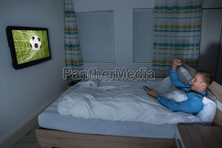 man watching football match on television