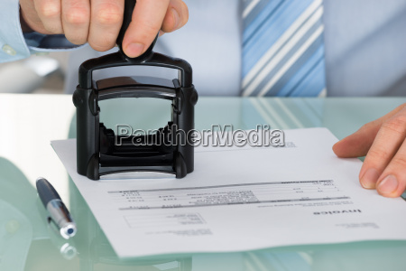 persons hand stamping document at office