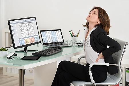 businesswoman suffering from backache in office