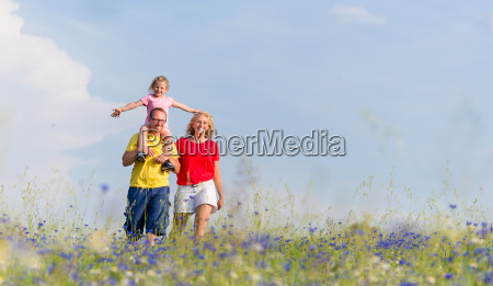 family is walking on meadow with