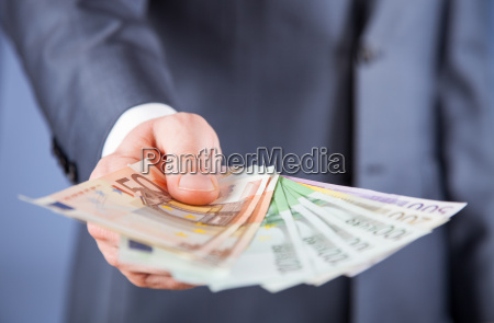 businessmans hand reaching out euro banknotes