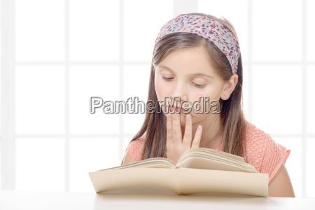 pre teenage girl reads a book