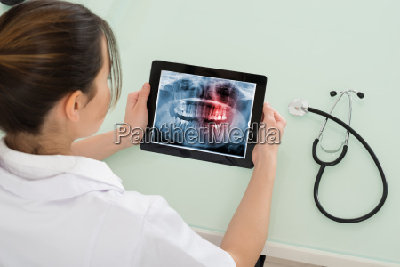 female doctor looking at dental x
