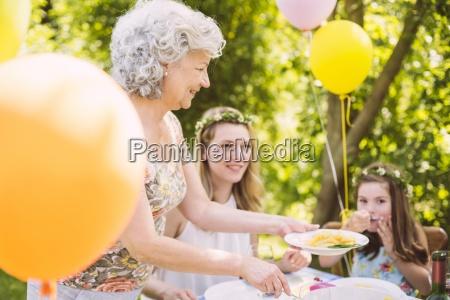 grandmother serving daughter and granddaughter pasta
