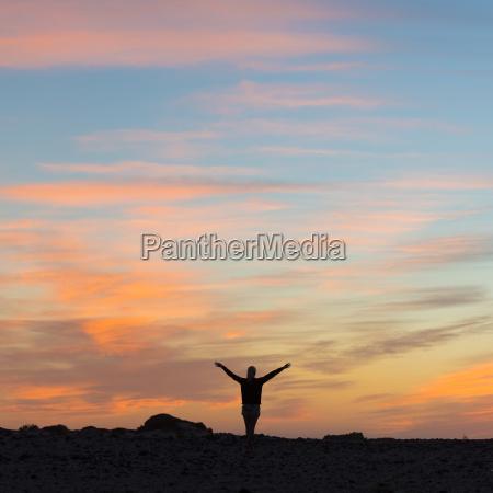 woman enjoying freedom at sunset