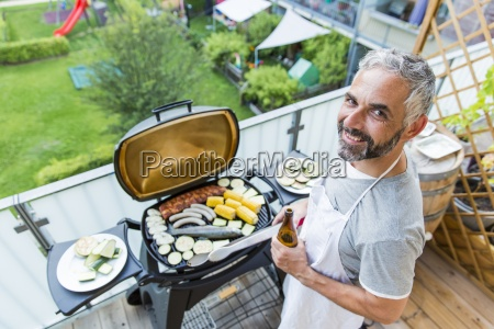smiling man barbecuing on his balcony