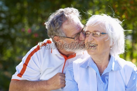 senior man kissing wife in park