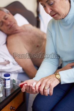 senior woman caring for sick husband