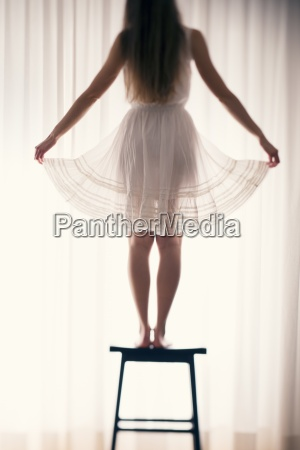 young woman standing on a stool