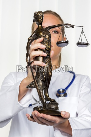 doctor holding lady justice figurine