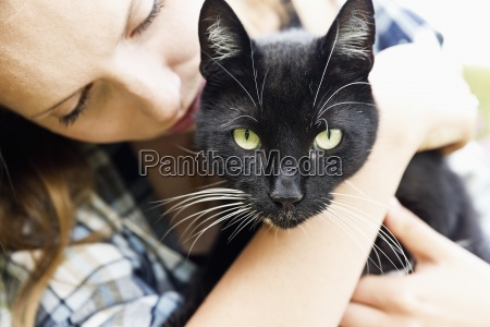 young woman holding black cat on