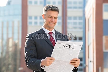 portrait of businessman reading newspaper