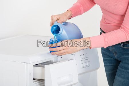 female hand pouring detergent in the
